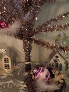 Tinsel tree, bird's nest, a white feather, and a broken snow baby.